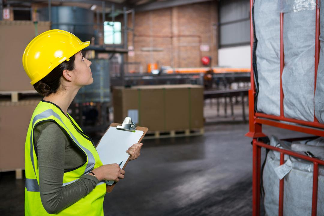 Side view of confident female worker examining products in warehouse