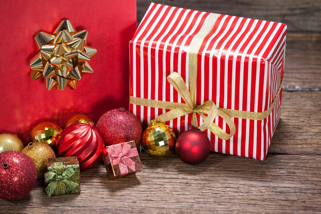 Red color Christmas decoration and gifts kept on wooden table during Christmas time