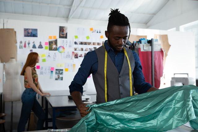 Front view of a young mixed race male fashion student with short hair and dreadlocks, looking at fabric while working on a design in a studio at fashion college, with another female student working in the background.