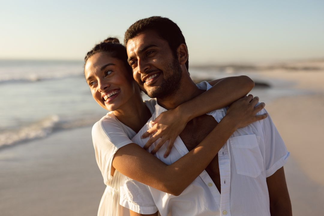 Happy young couple embracing each other on the beach