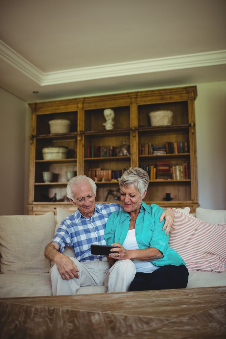 Senior couple using mobile phone in living room Photo from ...