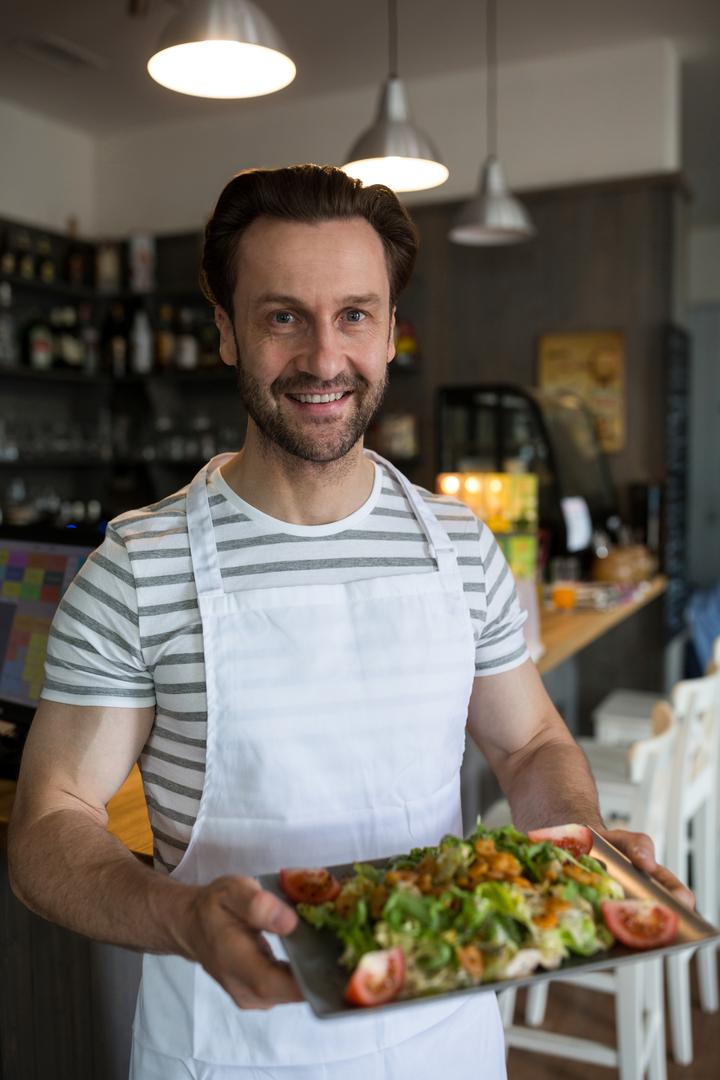 Portrait of smiling waiter carrying a tray of salad in restaurant