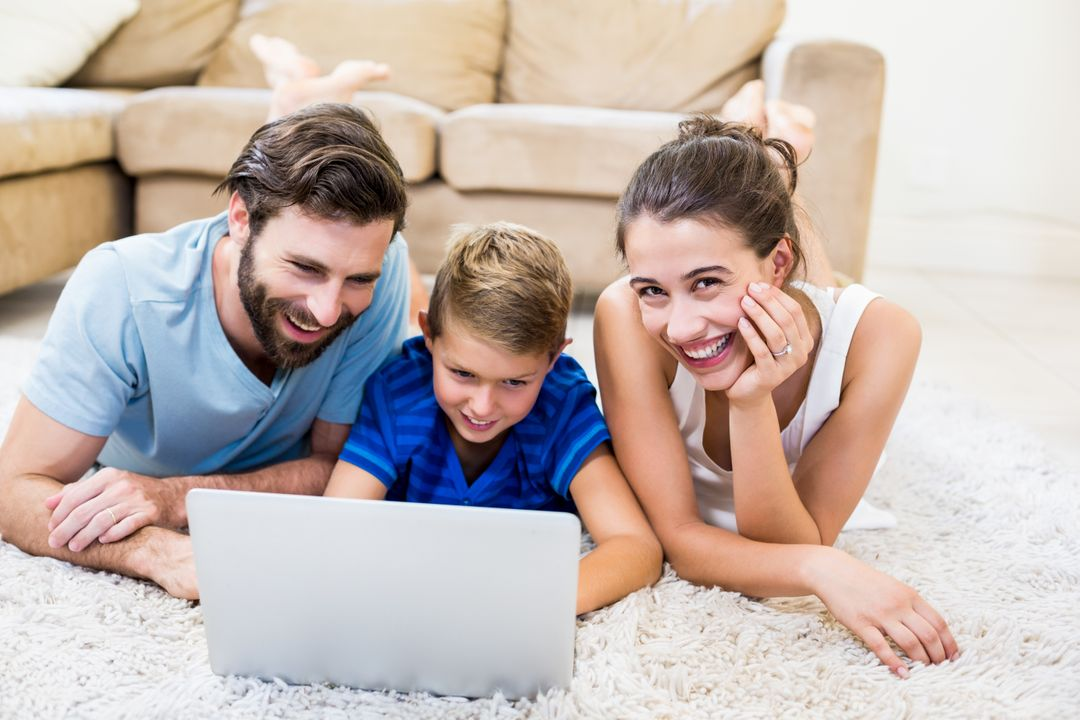 Parents and son lying on rug and using laptop at home