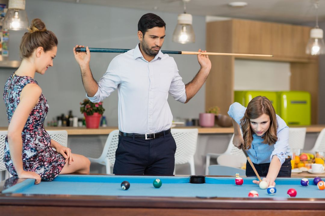 Smiling business colleagues playing pool in office space Free Stock Images from PikWizard