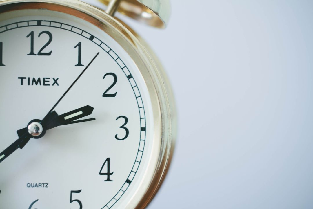Close of image of an alarm clock with the small dial pointing towards two