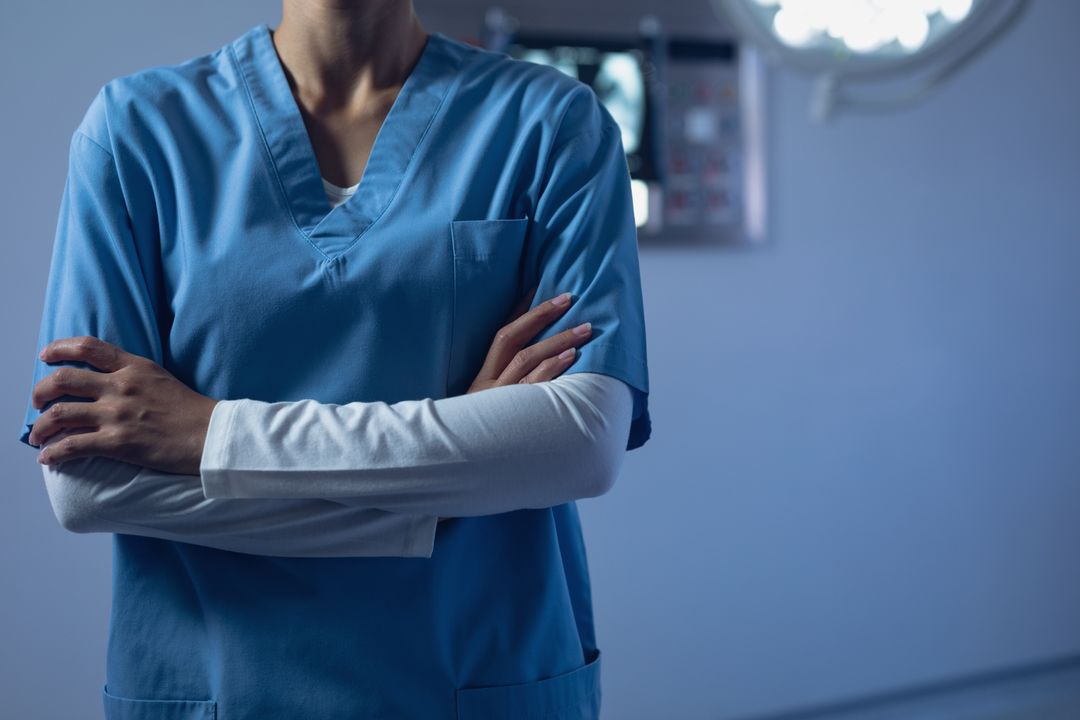 Mid section of female surgeon standing with arms crossed in operation theater at hospital