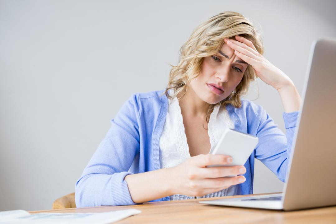 Stressed woman using mobile phone at home Free Stock Images from PikWizard
