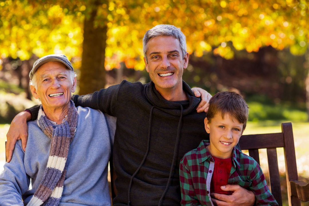 Portrait of man with father and son sitting at park during autumn Free Stock Images from PikWizard