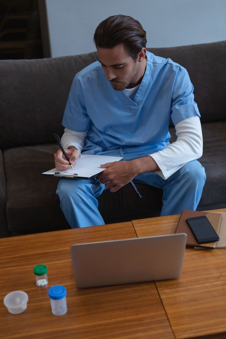 High angle view of male surgeon writing on clipboard while sitting on sofa in lobby at hospital