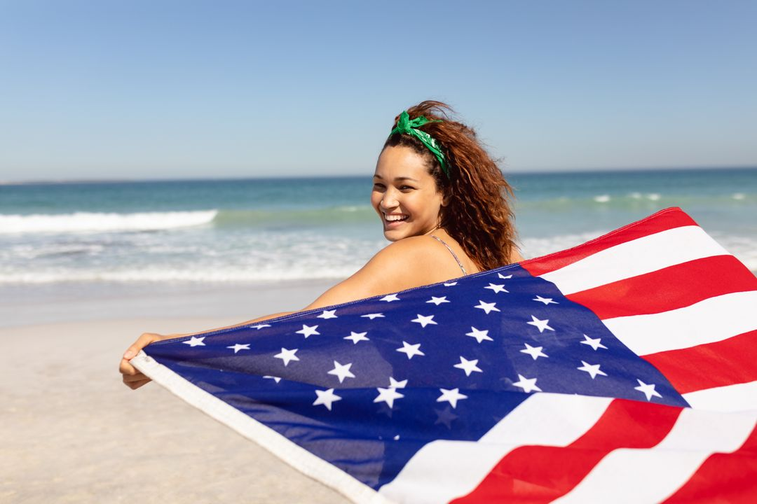 Rear view beautiful happy young Mixed-race woman waving american flag on beach in the sunshine