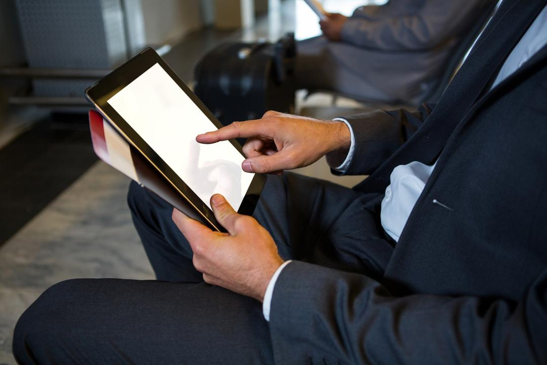 Mid-section of businessman using digital tablet while sitting at airport terminal Free Stock Images from PikWizard