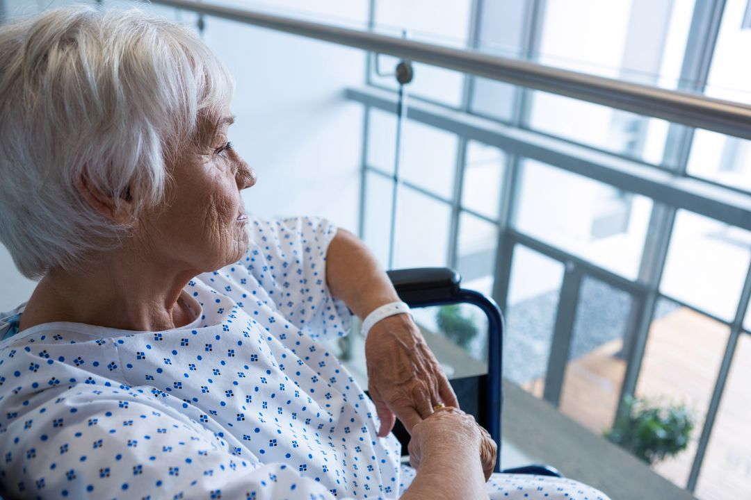 Thoughtful disabled senior patient on wheelchair in hospital passageway at hospital Free Stock Images from PikWizard