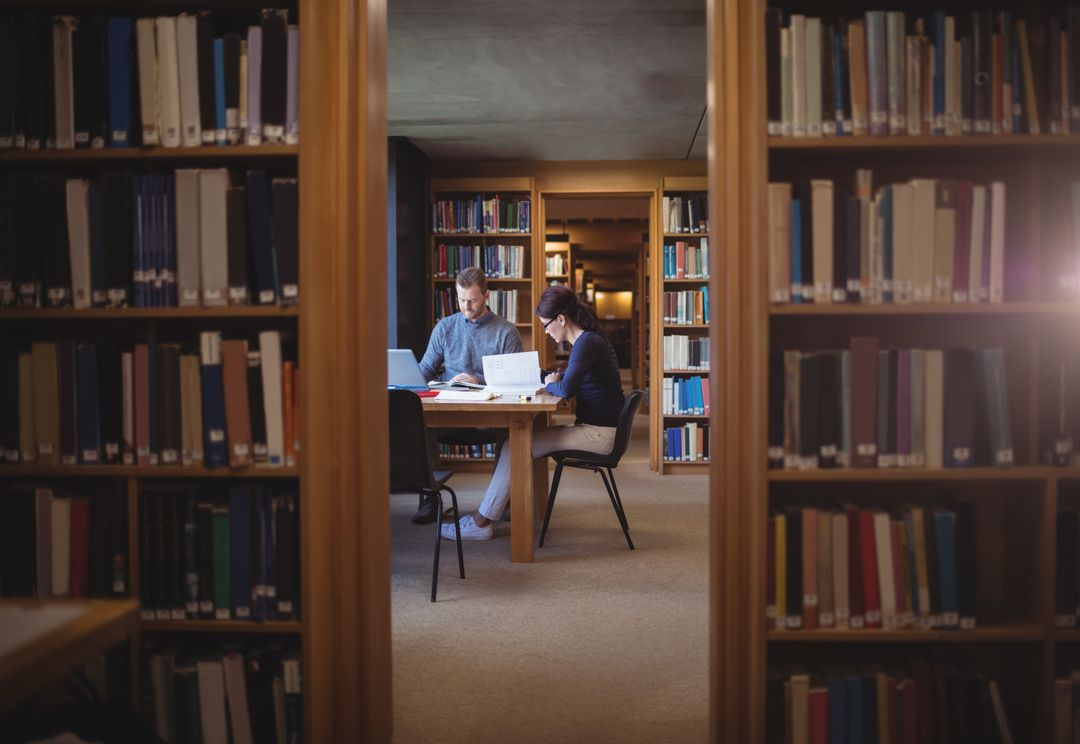 Wide Image of students working on desks in a library surrounded by shelves of books