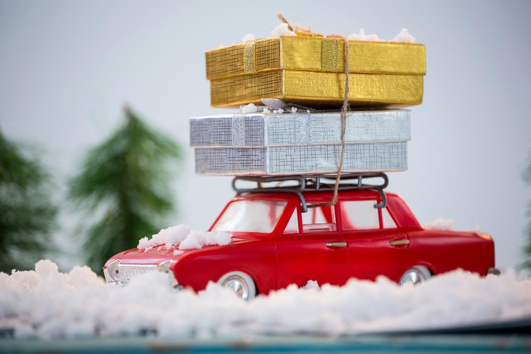 Toy car carrying christmas present on fake snow during christmas time Free Stock Images from PikWizard