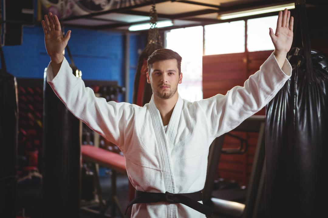 Karate player standing with arms spread in fitness studio
