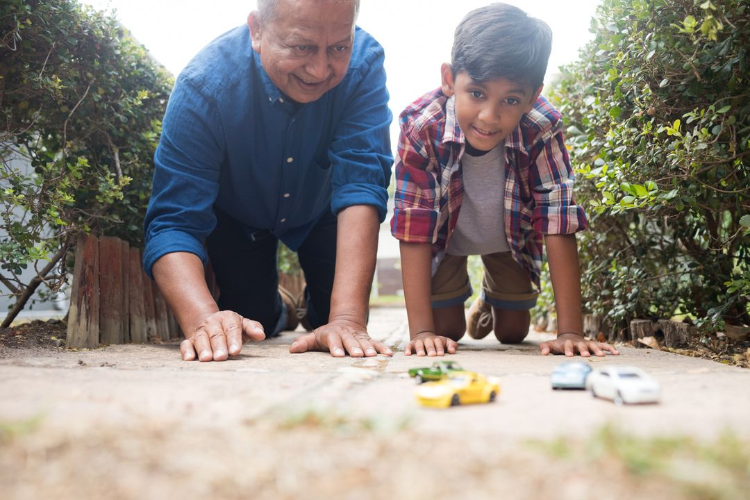 Boy and grandfather playing with toy cars while kneeling on pavement in yard Free Stock Images from PikWizard