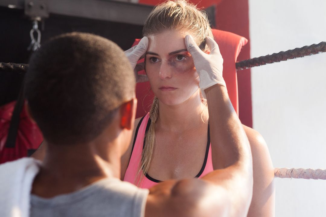 Trainer giving head massage to woman in boxing ring