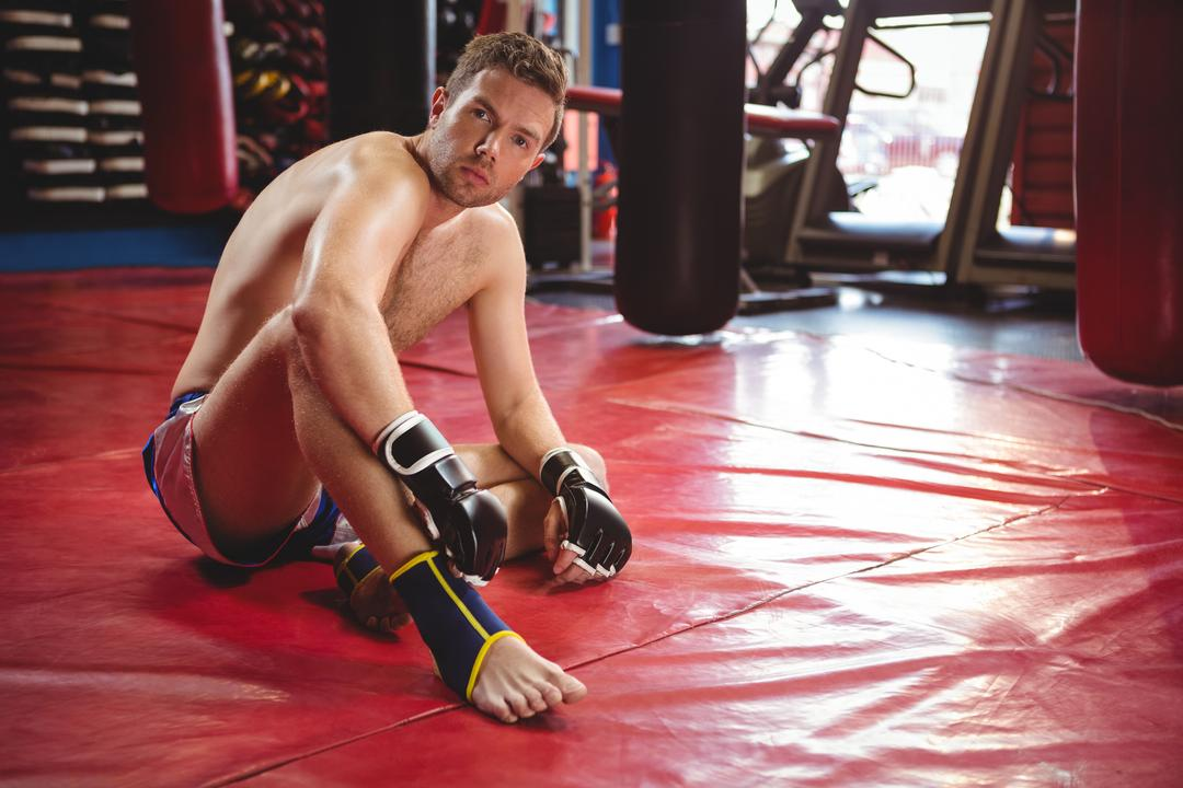 Portrait of tired boxer relaxing on floor in fitness studio Free Stock Images from PikWizard