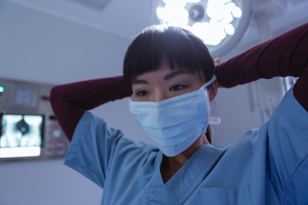 Front view of female surgeon wearing surgical mask in operation room at hospital