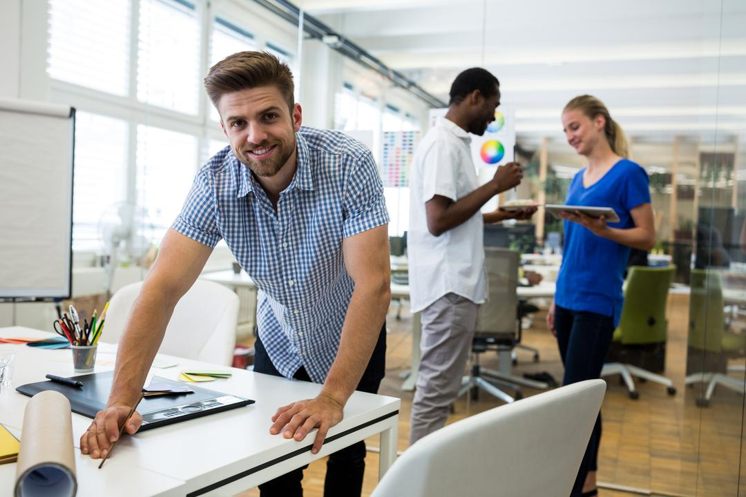 Portrait of male graphic designer smiling while coworkers interacting in background