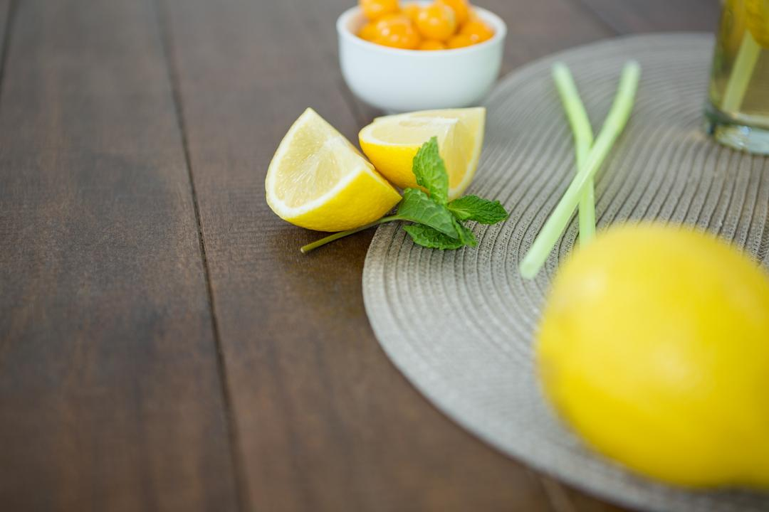 Close-up of lemon wedges and mint on wooden board