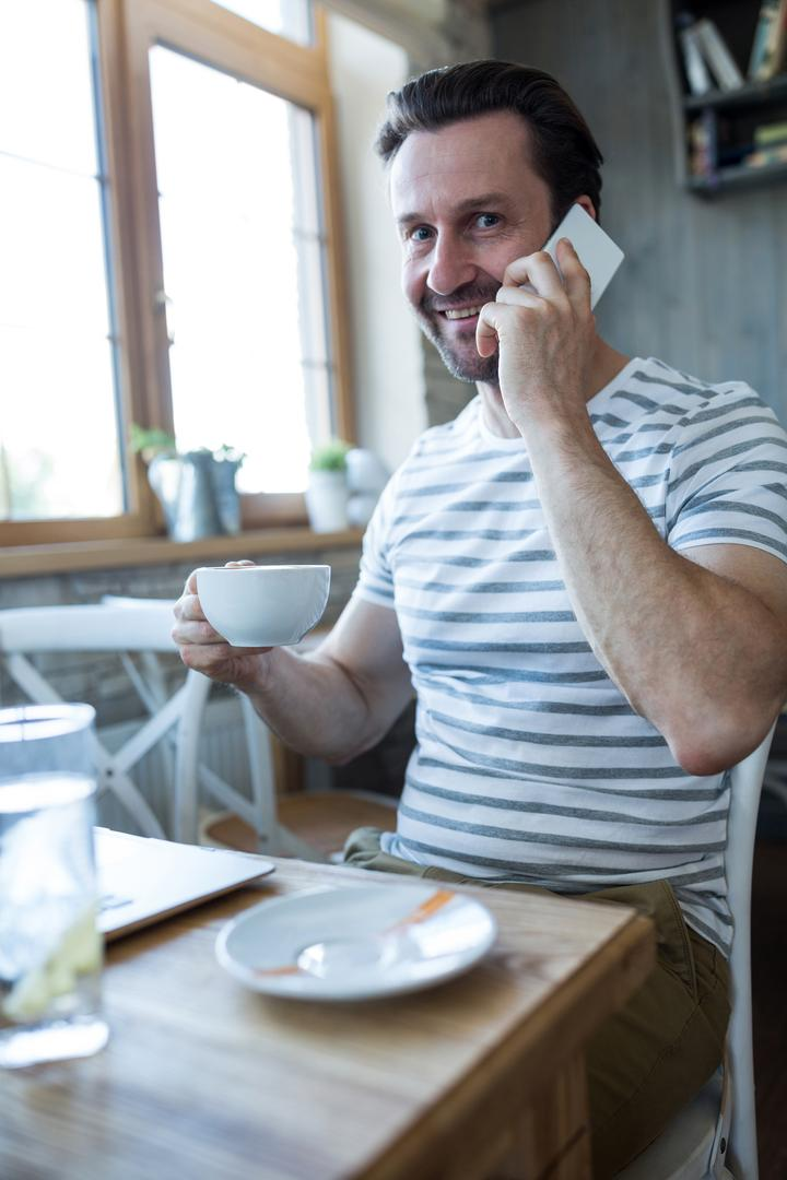 Smiling man holding a coffee cup and talking on the mobile phone in coffee shop
