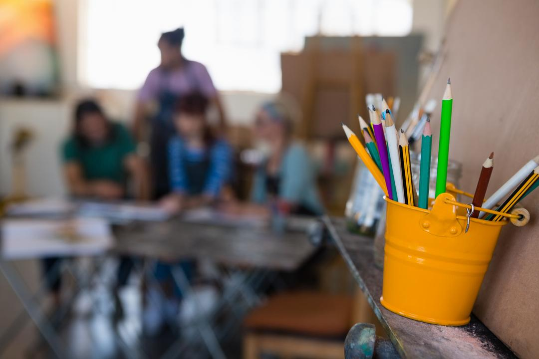 Close up of colored pencils in bucket on easel with students in background at art class Free Stock Images from PikWizard