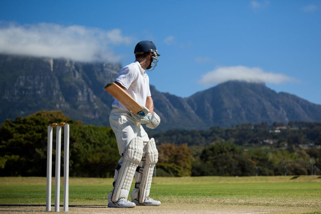 Full length of cricket player practicing against blue sky on field