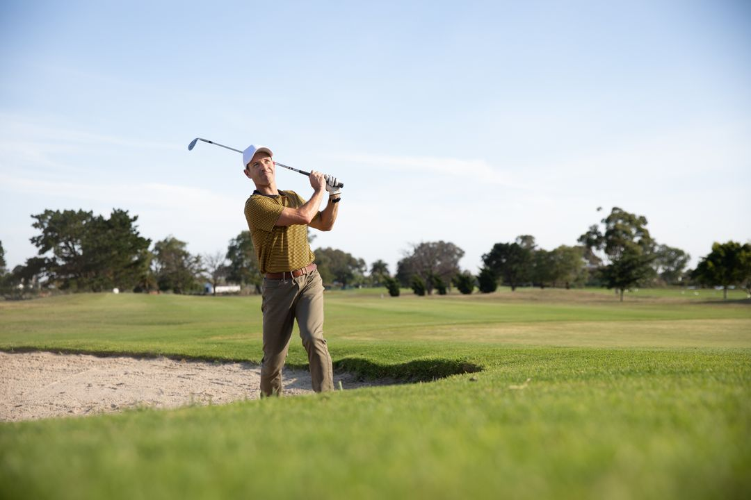 Caucasian male golfer practicing on a golf course on a sunny day wearing a cap and golf clothes, hitting a golf ball. Hobby healthy lifestyle leisure. Free Stock Images from PikWizard