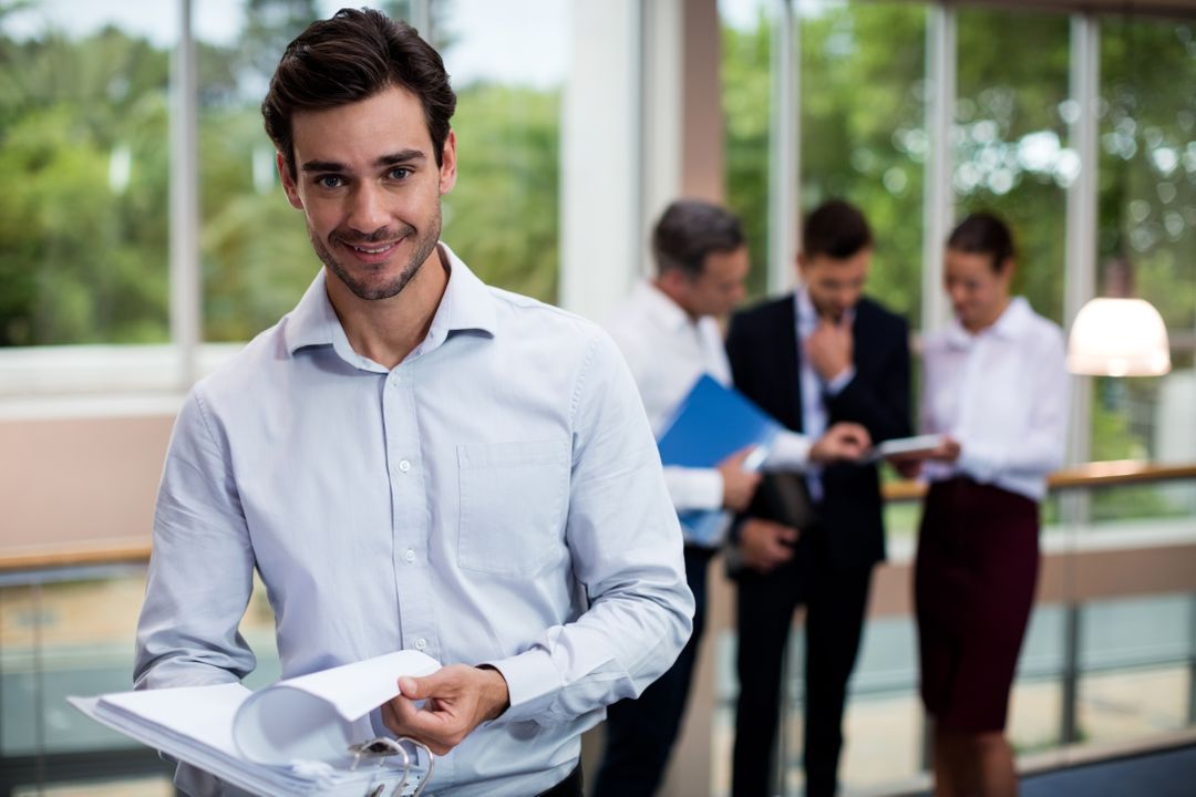 Portrait of male business executive holding document in conference center Free Stock Images from PikWizard