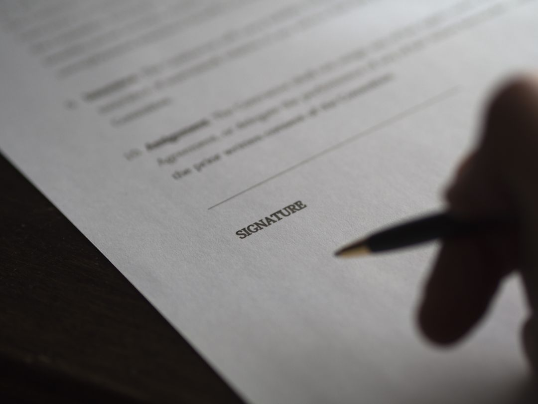 person holding pen over the signature section of a blurred business agreement