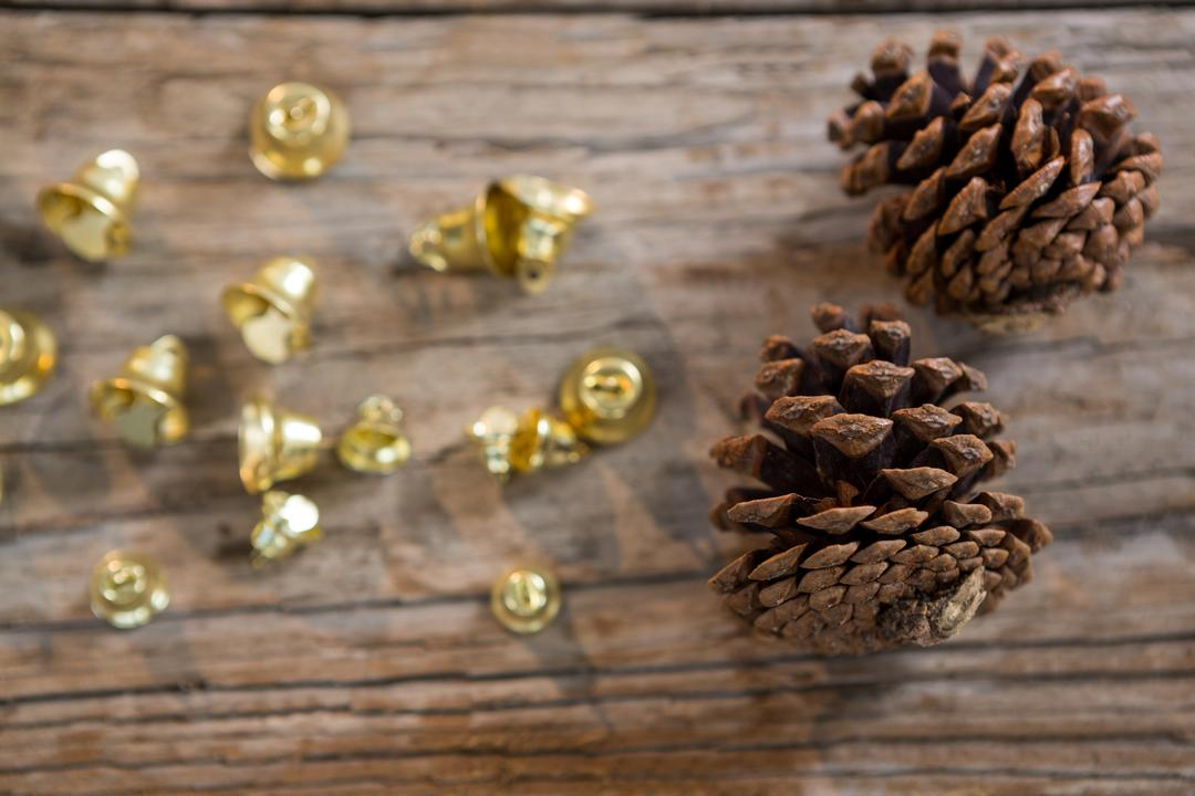 Christmas bells and pine cone on wooden plank during christmas time