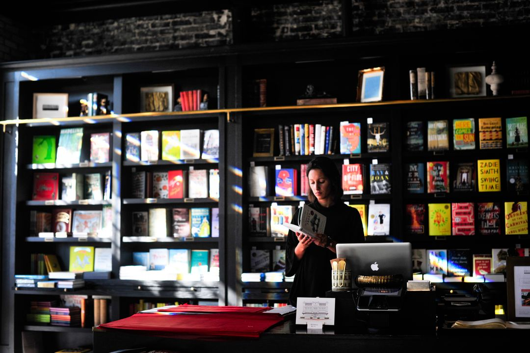 Woman standing in a book store reading a book while the sun shines through the window