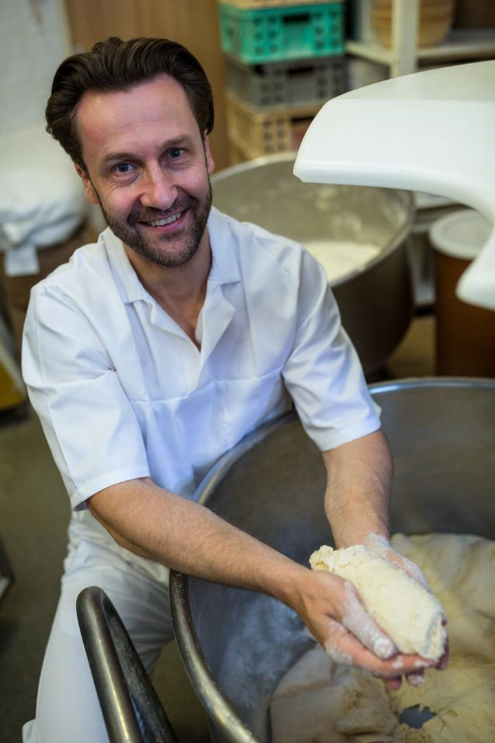 Portrait of smiling baker preparing dough