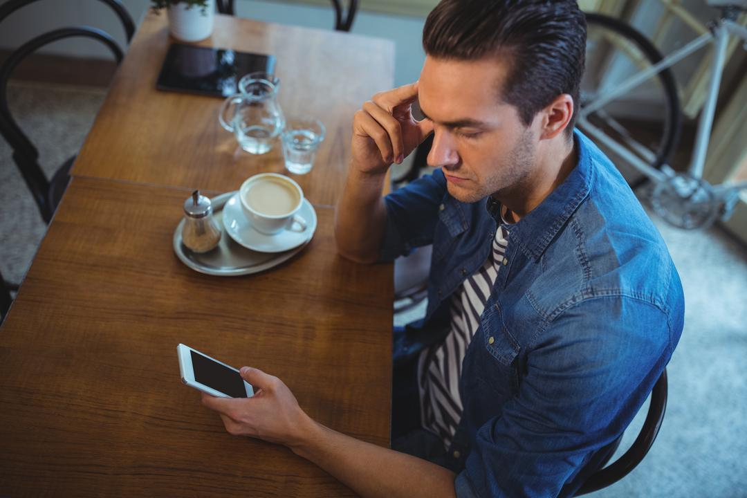 Man using mobile phone with cup of coffee on table in café