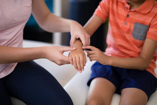 Midsection of female therapist examining hand with boy sitting on bed