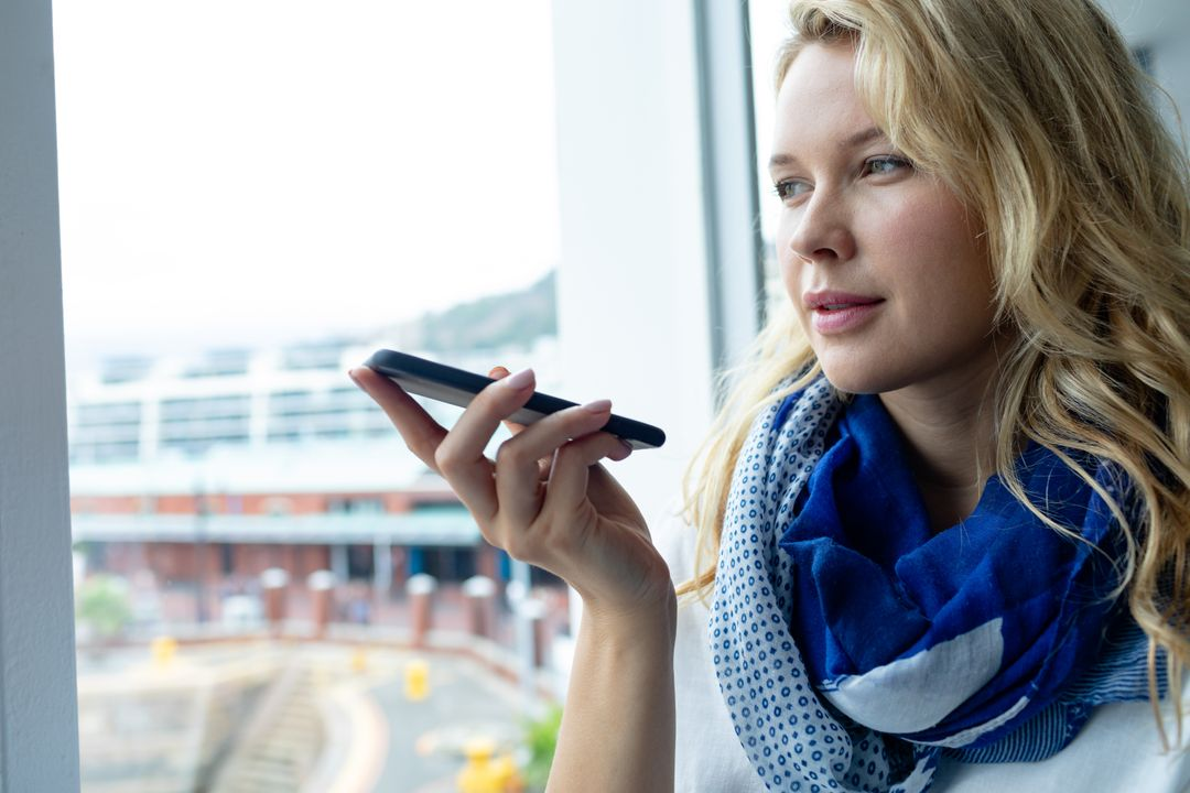 Front view of beautiful young caucasian businesswoman talking on mobile phone near window in a modern office