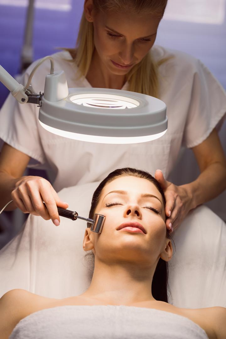 Dermatologist performing laser hair removal on patient face in clinic Free Stock Images from PikWizard