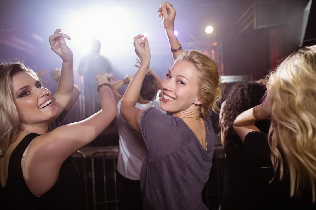 Young female friends dancing at nightclub during music festival Free Stock Images from PikWizard