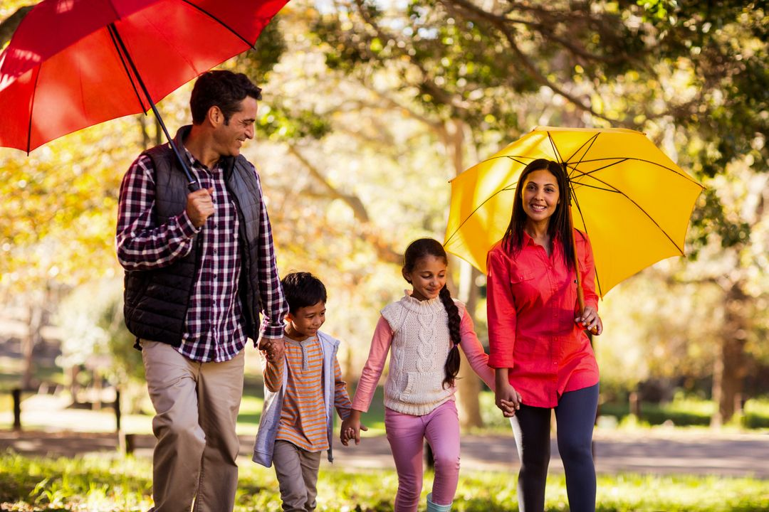 Happy family walking with umbrellas at park during autumn