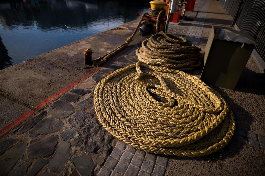Spiral mooring rope kept in harbor on a sunny day
