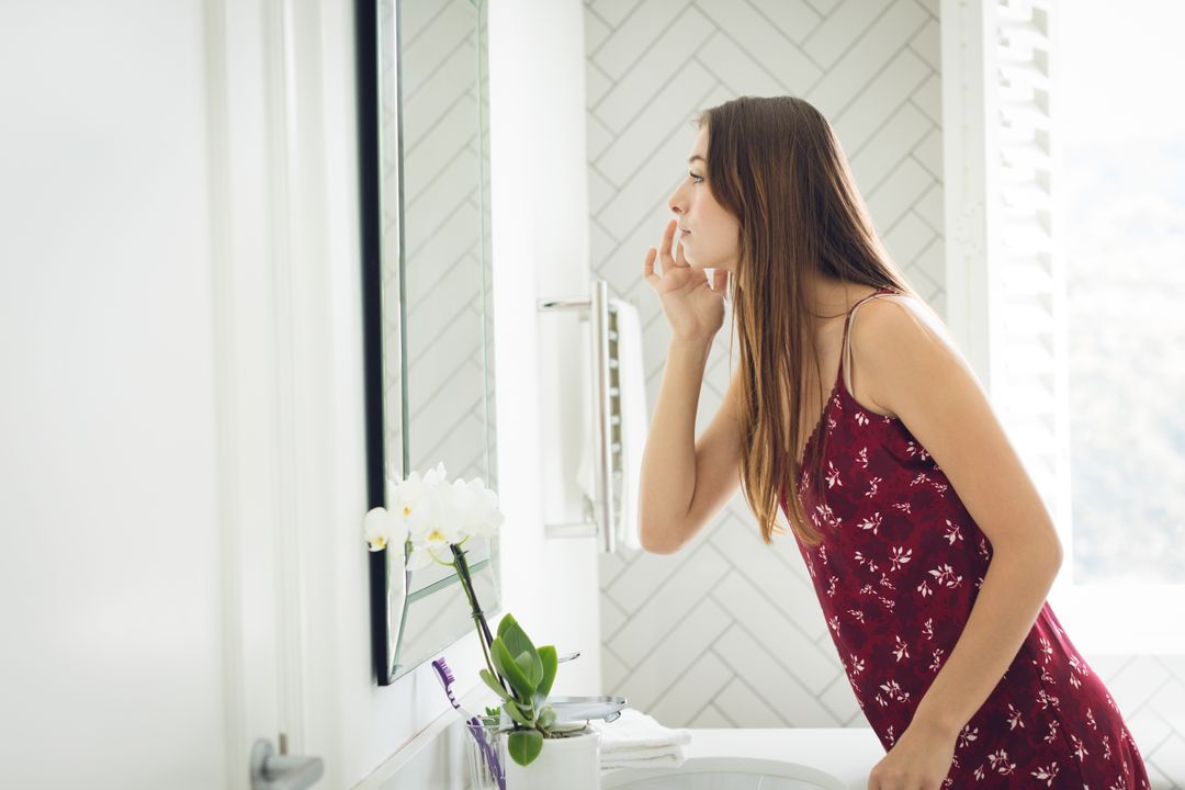 Side view of beautiful woman examining her face in bathroom at comfortable home