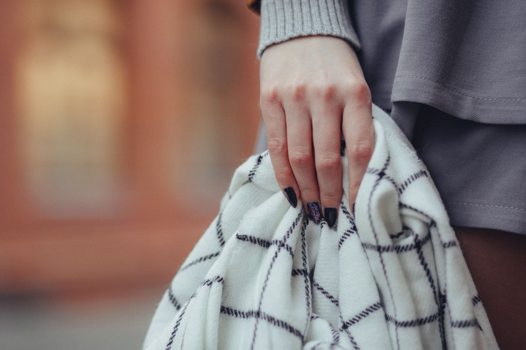 Woman holding a black and white scarf with long nails in a urban street