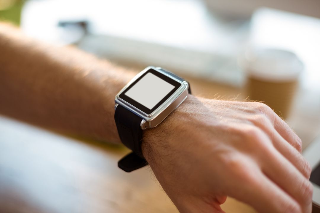 Close-up of hand wearing a smartwatch in office Free Stock Images from PikWizard