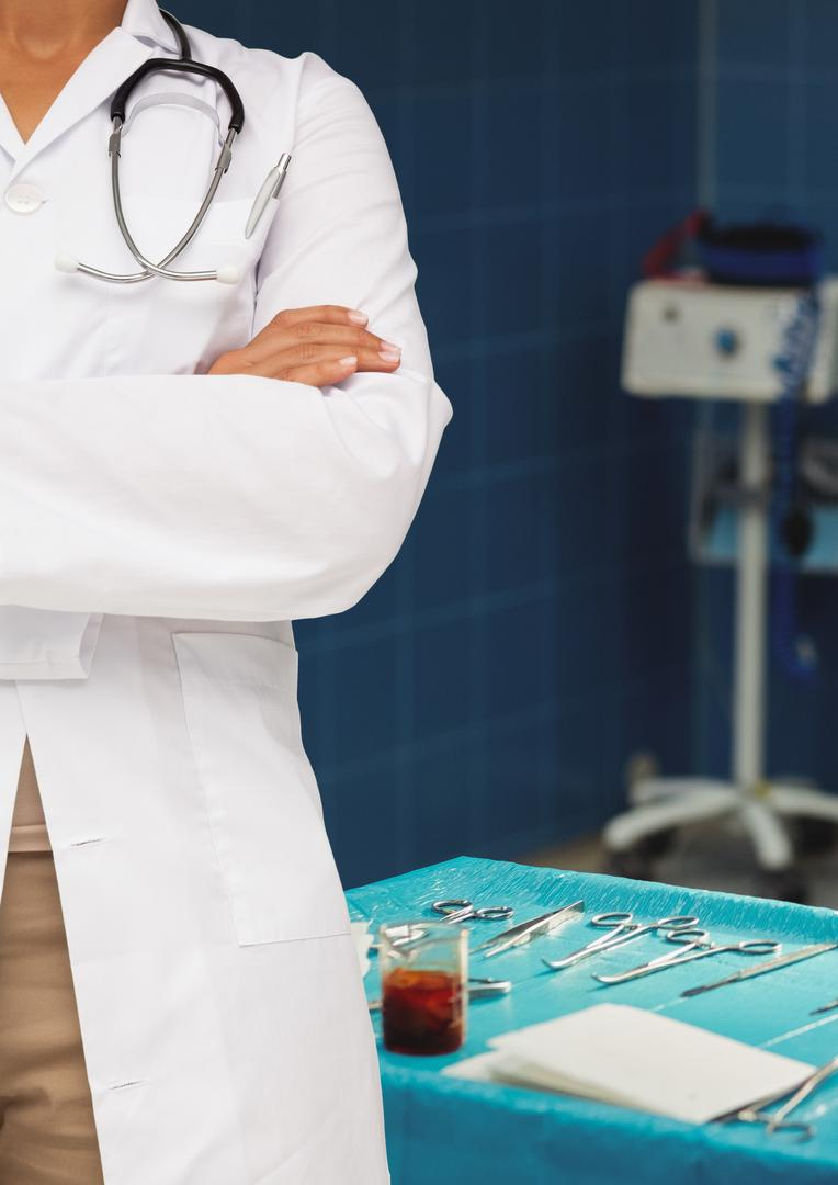 Mid section of doctor standing with arms crossed with medical instruments in background Free Stock Images from PikWizard
