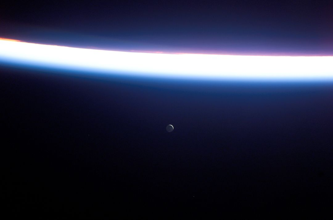 S114-E-7558 (6 August 2005) --- This view featuring a distant Moon and a line of airglow of Earth's atmosphere was photographed by an STS-114 crewmember onboard the Space Shuttle Discovery after departure from the international space station. Free Stock Images from PikWizard