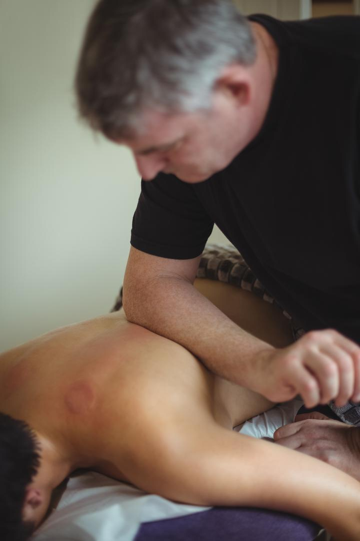 Man receiving massage from therapist in spa