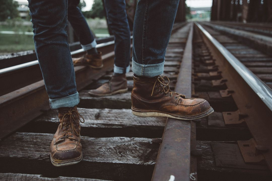 Person Wearing Blue Denim Jeans and Brown Leather Shoes Standing in Railway during Daylight