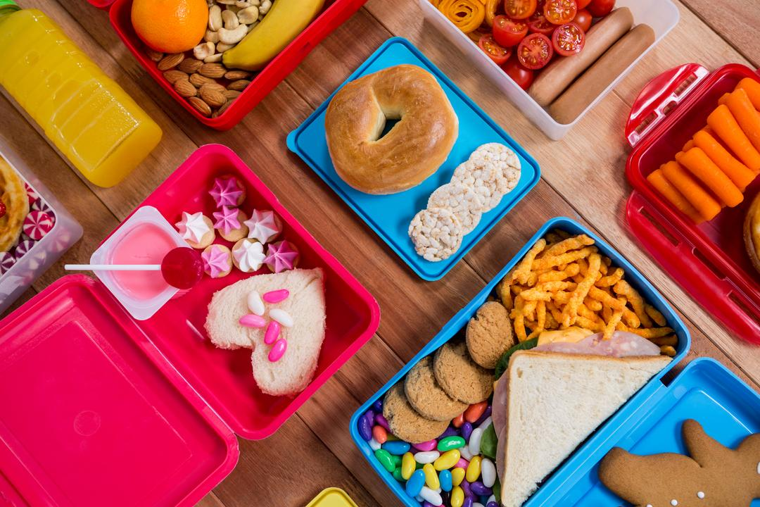 Lunch box with various snack and sweet food on wooden table