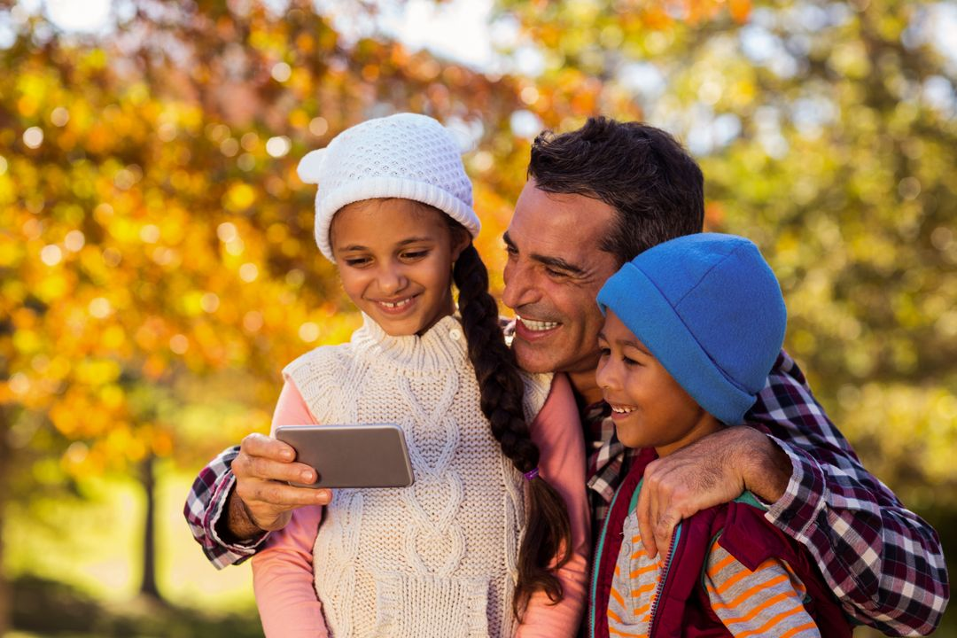 Happy father with children looking at mobile phone at park during autumn Free Stock Images from PikWizard